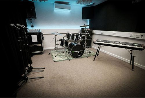 Drum kit, piano and microphones set up in a studio